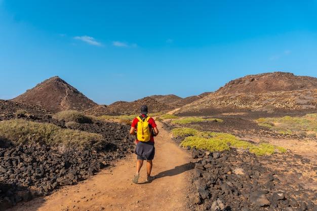 Un jeune homme avec un sac à dos jaune sur le sentier en direction nord vers isla de lobos, le long de la côte nord de l'île de fuerteventura, îles canaries. espagne
