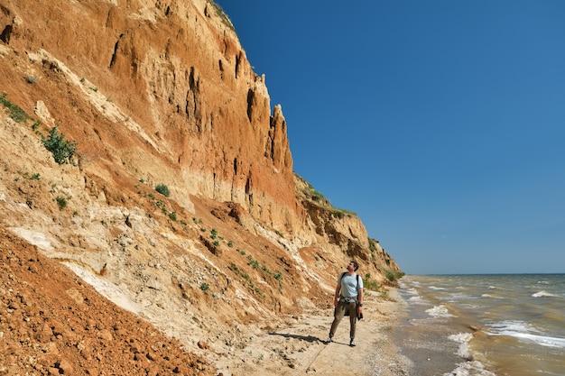 Jeune homme et sac à dos marchent seuls le long d'une colline de sable au-dessus de la mer.