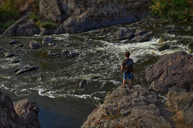 Un jeune homme avec un sac à dos se tient sur les rochers près d'une rivière sauvage photo de dos le concept de t...