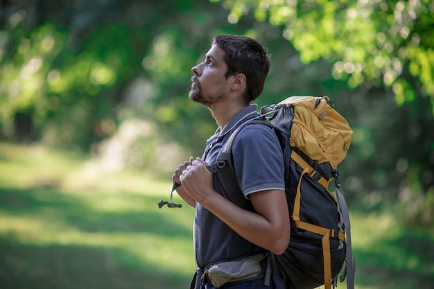 Jeune homme de sac à dos souriant dans la nature de la forêt d'été. heureux beau mâle étudiant adulte regardant la caméra marche randonnée en arrière-plan de la forêt. sac d'école ou concept de voyage de randonnée.