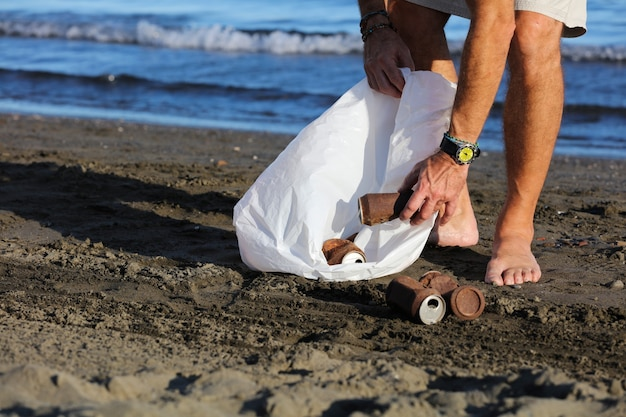 Jeune homme avec sac poubelle et boîtes rouillées à l'intérieur sur la plage