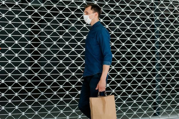 Jeune homme avec des sacs à provisions marchant le long d'une rue de la ville. coronavirus en ville