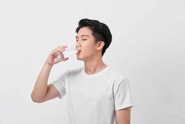 Jeune homme sain et heureux buvant de l'eau tout en se relaxant à la maison
