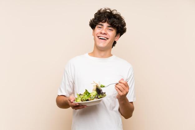 Jeune homme avec une salade sur un mur vert isolé