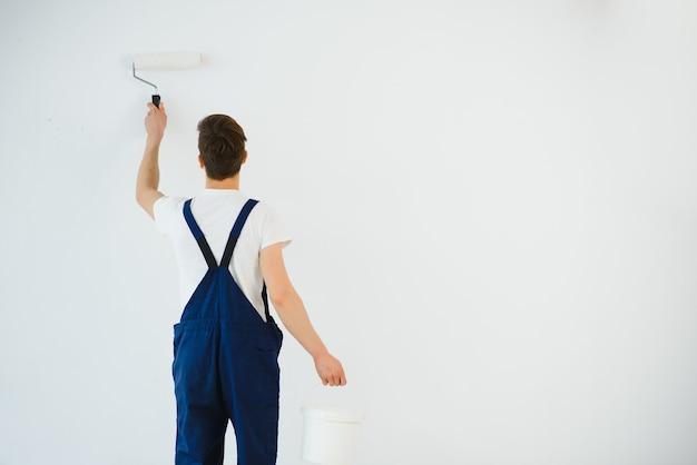 Jeune homme en salopette bleue peinture mur en couleur blanche avec un rouleau