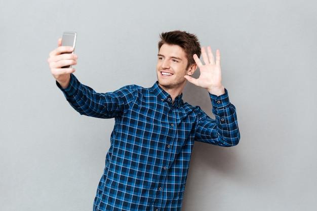 Jeune homme saluant avec quelqu'un tout en faisant un appel vidéo ou un selfie