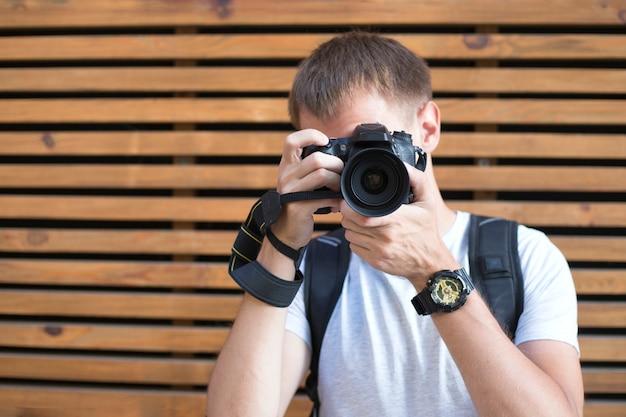 Jeune homme sans visage avec appareil photo reflex numérique sur le fond en bois