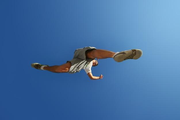 Jeune homme sautant par-dessus la caméra au-dessus du ciel bleu