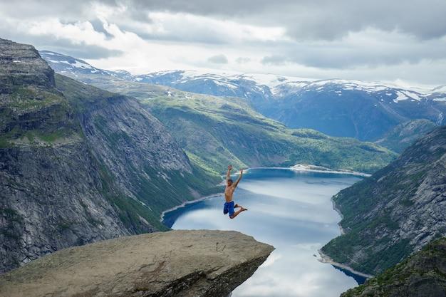 Jeune homme saute sur le bord trolltunga. norvège.