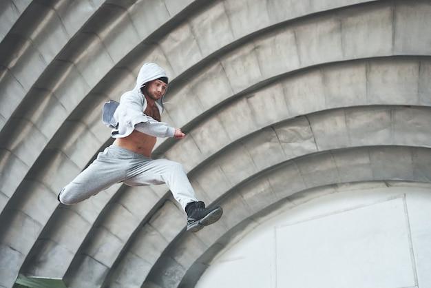 Un jeune homme saute. parkour en espace urbain, activité sportive.
