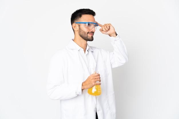 Jeune homme scientifique isolé sur un mur blanc ayant des doutes et de la pensée