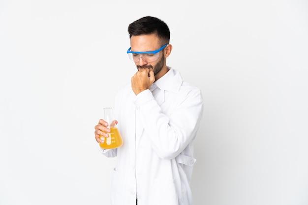 Jeune homme scientifique isolé sur un mur blanc ayant des doutes
