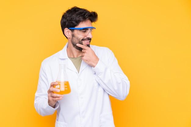 Jeune homme scientifique sur mur jaune isolé en pensant à une idée et à côté