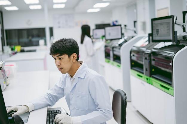 Jeune homme scientifique à la recherche des résultats du rapport de l'analyseur de sang d'automatisation dans l'ordinateur et de la jeune femme scientifique travaillant avec l'analyseur de sang
