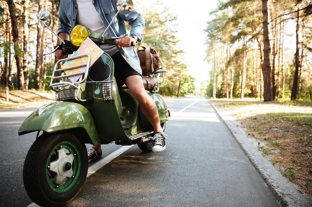 Jeune homme en scooter à l'extérieur.