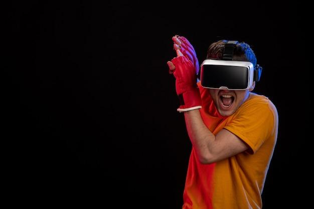 Jeune homme se battre en réalité virtuelle avec des gants mma sur surface noire