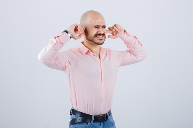 Jeune homme se branchant les oreilles avec les doigts tout en devenant fou en chemise rose, jeans, vue de face.