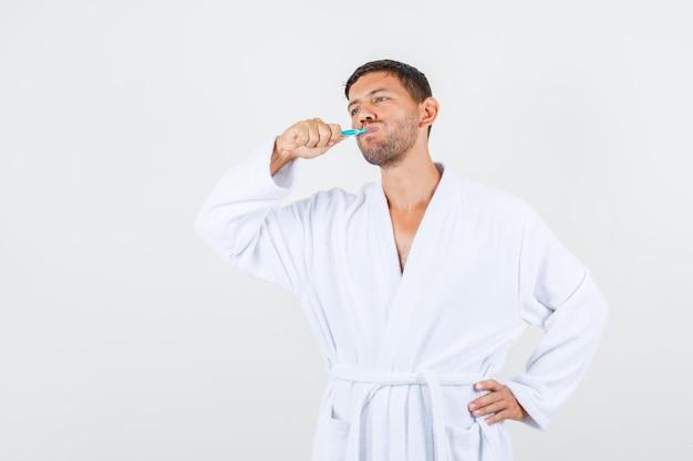Jeune homme se brosser les dents avec la main sur la taille en peignoir blanc et regardant pensif, vue de face.