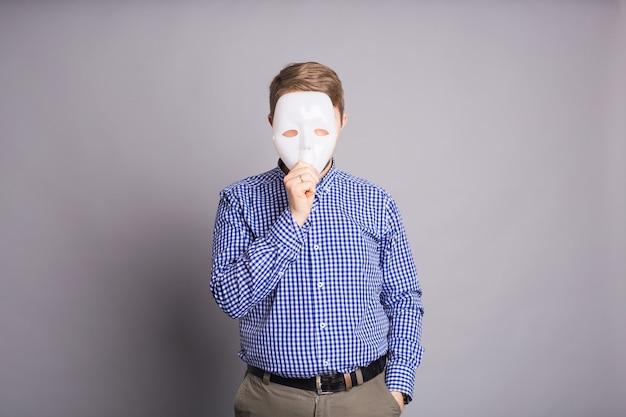 Jeune homme se cachant derrière un masque blanc sur un mur gris.