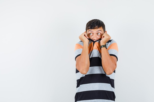 Jeune homme se cachant le visage derrière le col en t-shirt et à la peur