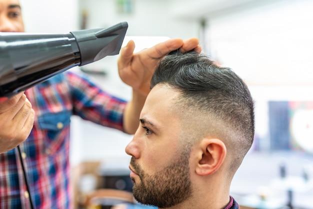 Jeune homme se coiffer dans un salon de coiffure.