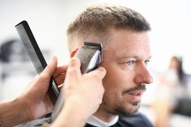 Jeune homme se coupe de cheveux avec tondeuse et ciseaux au portrait de salon de coiffure