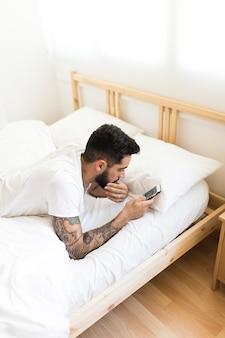Jeune homme se détendre sur le lit à l'aide de téléphone portable