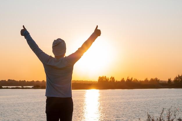 Un jeune homme se dresse sur un lac au coucher du soleil