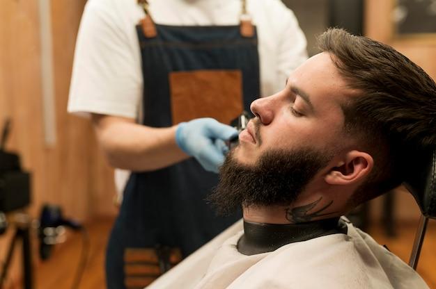 Jeune homme se faisant coiffer sa barbe chez le coiffeur