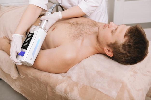 Jeune homme se fait masser les endosphères à la clinique de beauté