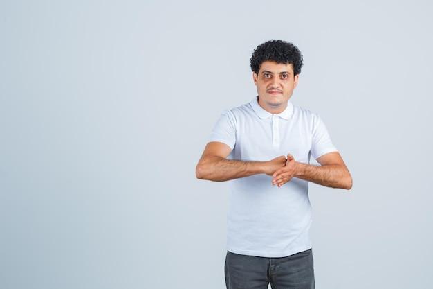 Jeune homme se frottant les mains dans un t-shirt blanc et un jean et à l'air sérieux, vue de face.