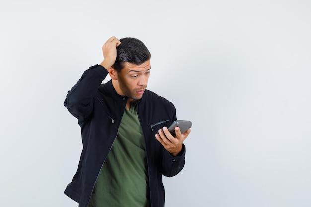 Un jeune homme se grattait en regardant une calculatrice en t-shirt, une veste et avait l'air perplexe, vue de face.