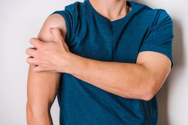 Jeune homme se gratte le concept de la main des maladies et des démangeaisons