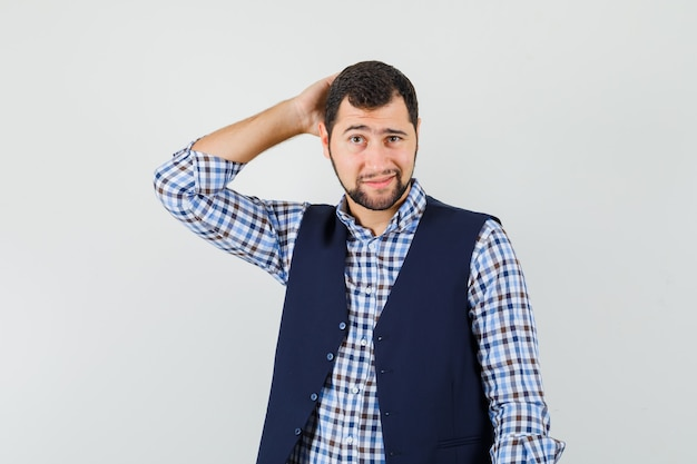 Jeune homme se gratte la tête en chemise, gilet et à la pensif.