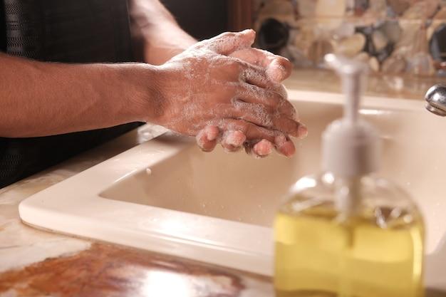 Jeune homme se lavant les mains avec de l'eau chaude au savon