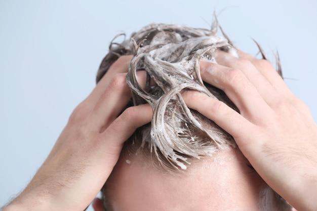Jeune homme se laver les cheveux sur fond de couleur, gros plan