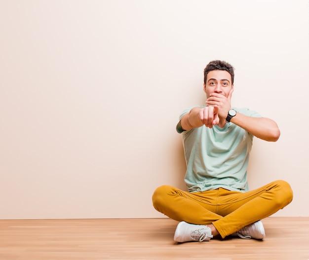 Jeune homme se moquant de vous, pointant vers la caméra et se moquant de vous ou se moquant de vous assis sur le sol