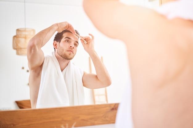 Jeune homme se peignant les cheveux debout près du miroir dans la salle de bain le matin
