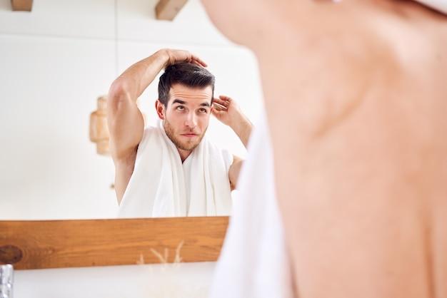 Jeune homme se peignant les cheveux en se tenant debout avec une serviette blanche sur le cou près du miroir dans la salle de bain