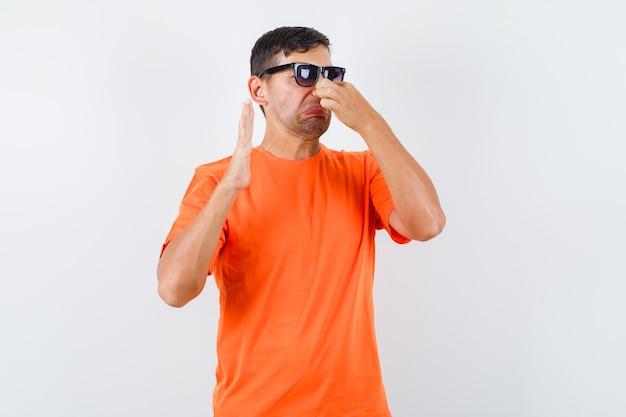 Jeune homme se pincer le nez en raison d'une mauvaise odeur en t-shirt orange et à la dégoûté
