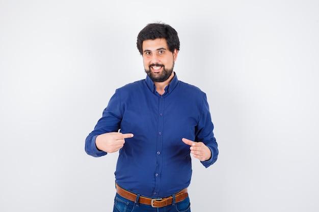 Jeune homme se pointant en chemise bleue et jeans et à l'optimisme. vue de face.