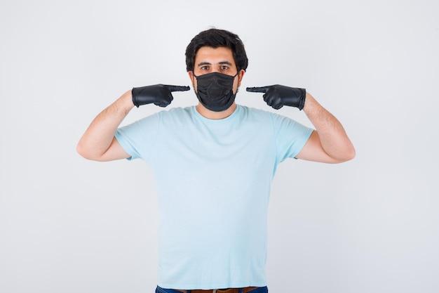 Jeune homme se pointant avec les doigts en t-shirt et ayant l'air confiant. vue de face.