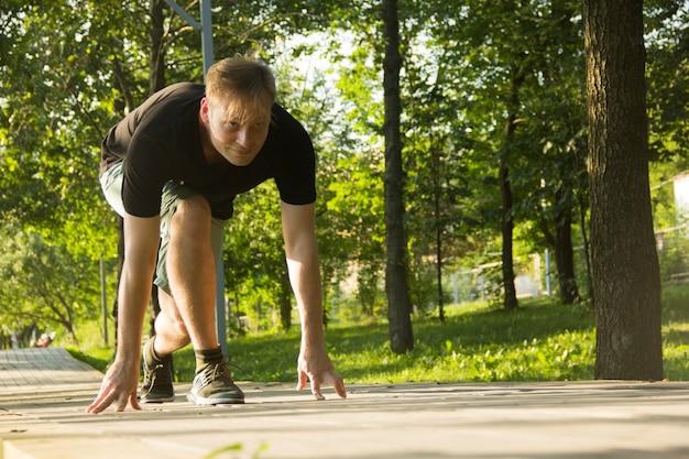 Un jeune homme se prépare à courir l'homme se prépare à courir à partir d'un faible départ