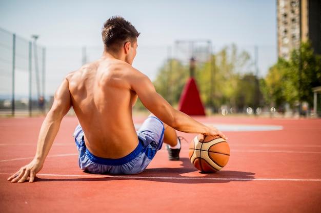 Jeune homme se reposant de jouer au basketball