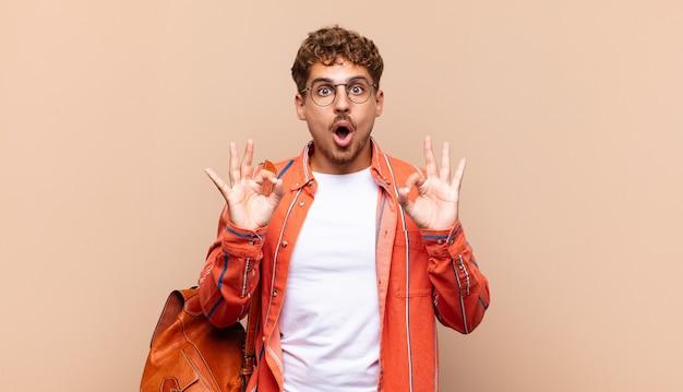 Jeune homme se sentant choqué, étonné et surpris, montrant son approbation en faisant signe à deux mains. concept étudiant