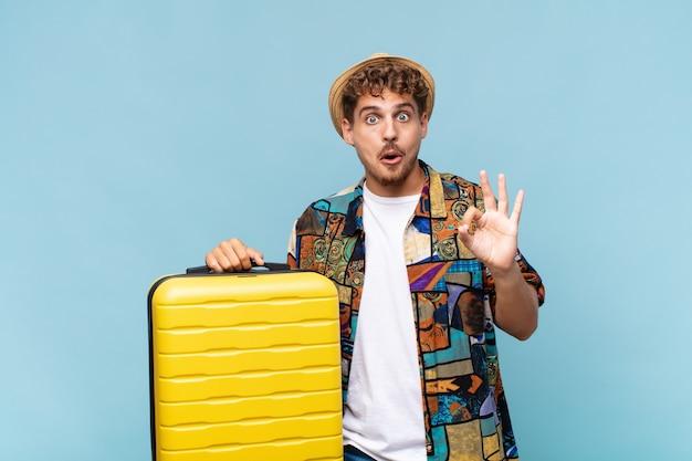 Jeune homme se sentant choqué, étonné et surpris, montrant son approbation en faisant signe avec les deux mains. concept de vacances