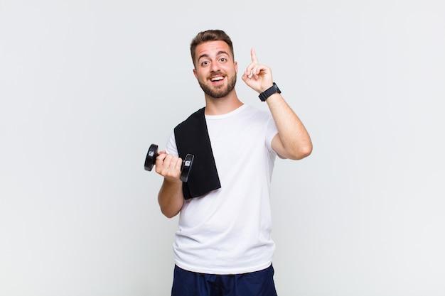 Jeune homme se sentant comme un génie heureux et excité après avoir réalisé une idée, levant joyeusement le doigt, eureka!