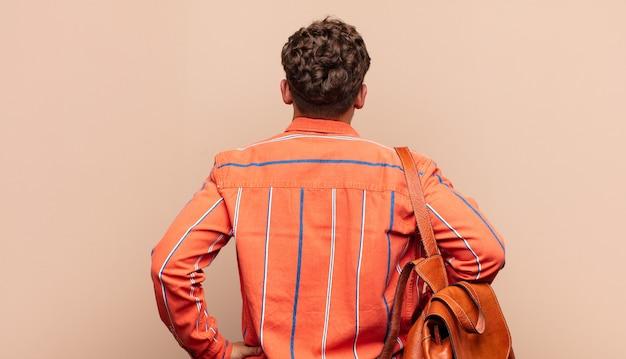 Jeune homme se sentant confus ou plein ou doutes et questions, se demandant, les mains sur les hanches, vue arrière. concept étudiant