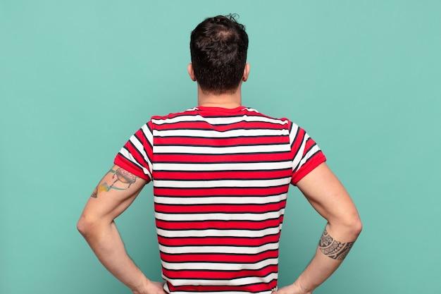 Jeune homme se sentant confus ou plein ou des doutes et des questions, se demandant, avec les mains sur les hanches, vue arrière