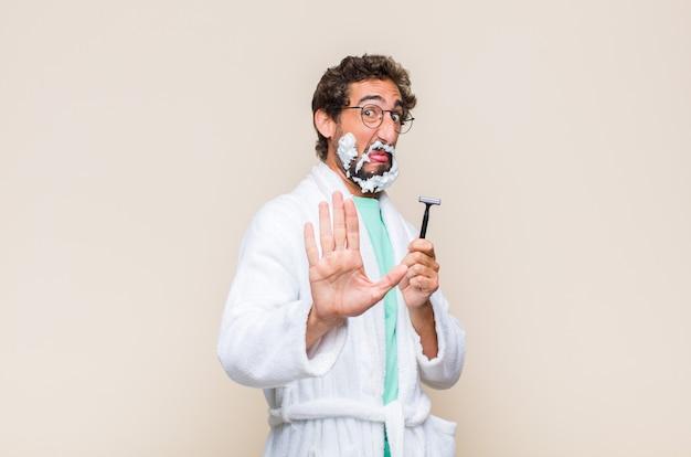 Jeune homme se sentant dégoûté et nauséeux, s'éloignant de quelque chose de méchant, malodorant ou puant, disant beurk